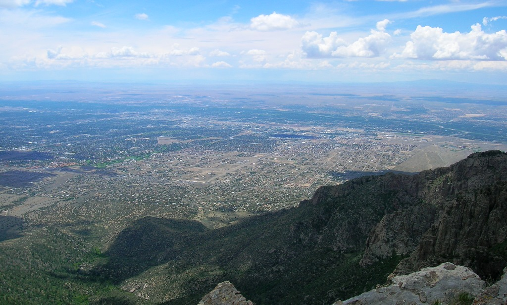 Looking down on Albuquerque from Sandia Crest on a bright spring day with white clouds against the cerulean blue sky