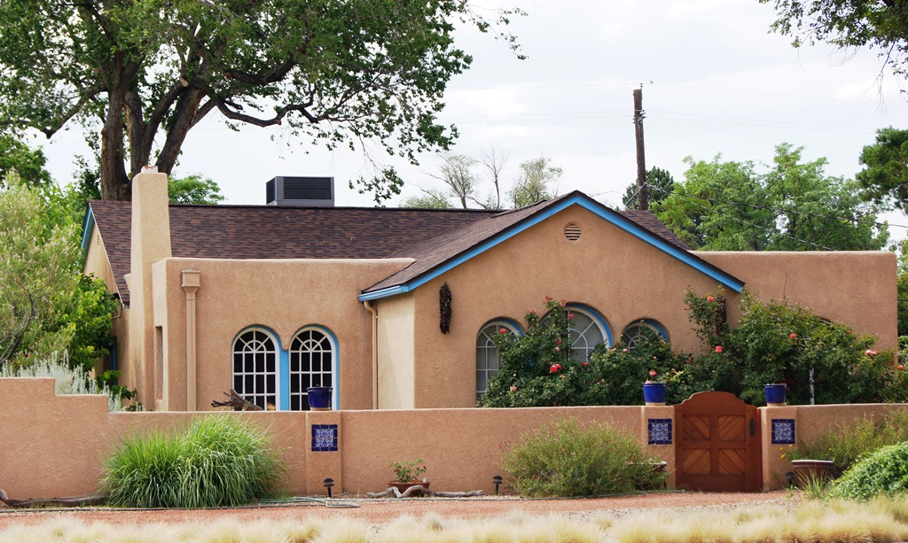 A mixed style, part territorial part phuble style home with tan stucco and blie trim on Monte Vista Blved in Albuquerque's University District